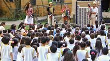 Imagem mostra o grupo de estudantes acompanhando a apresentação do espetáculo de mamulengos (teatro de bonecos)