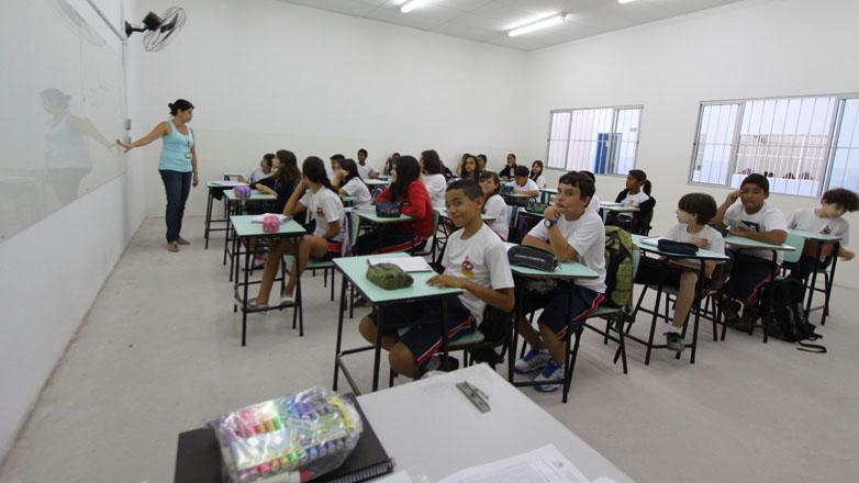 Professora em primeiro plano ensina alunos durante aula em escola municipal de São José dos Campos
