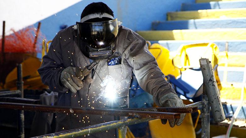 Imagem mostra operário executando solda em placa de metal