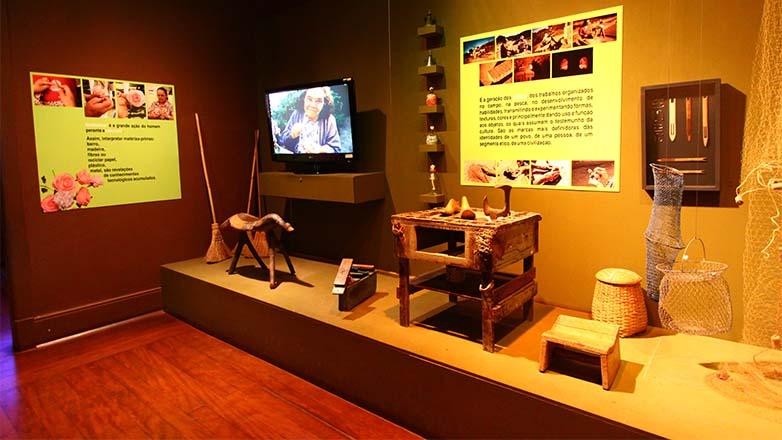 Interior do Museu do Folclore, mostrando objetos que estão em exposição, e vídeo reproduzido em TV