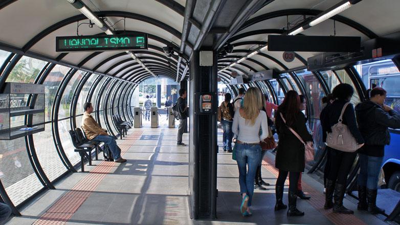 BRT em Curitiba, pessoas esperam o transporte nos pontos