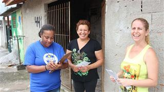 Agentes ambientais nas ruas explicando sobre a ação e distribuindo folders aos moradores