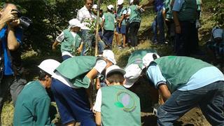 Crianças da Fundhas realizando plantio de mudas em nascente