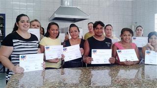 Alunas do curso de panificação e confeitaria com certificados de conclusão em mãos