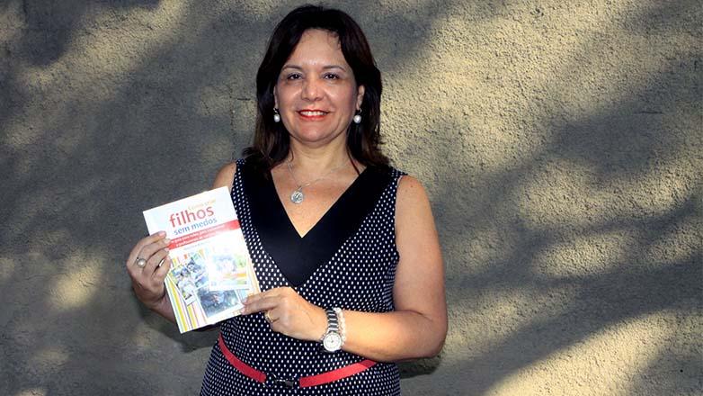 Imagem mostra a autora com o livro nas mãos