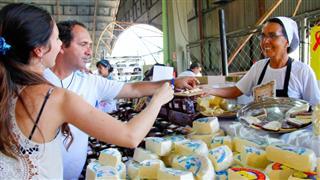 Participantes  da festa compram queijo em barraca