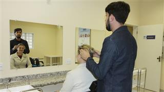 Cabeleiro atende mulher durante aula prática